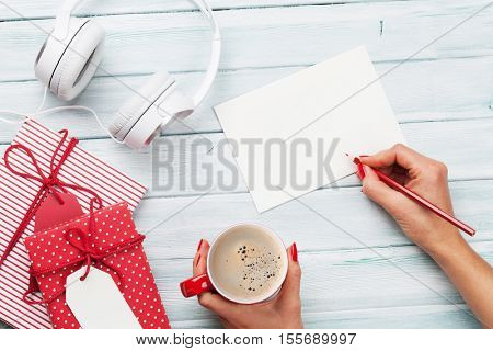 Female writing greeting card and wrapping christmas gifts. Top view with copy space