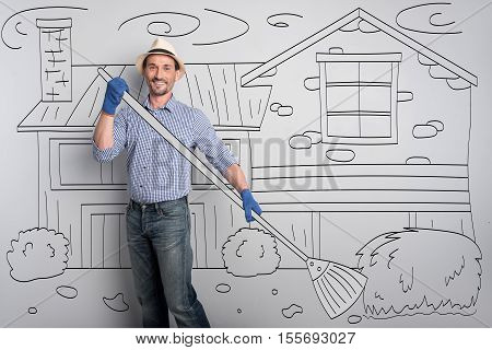 Sweet home. Young good looking man smiling and holding broom while standing in the yard.y farmer cleaning the yard.