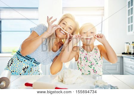 Playful Mum and daughter with pastry mustaches baking together in the kitchen preparing a mound of dough high key background with copy space