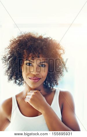 Young pretty black girl with curly hair smiling at camera on blurred inside background.