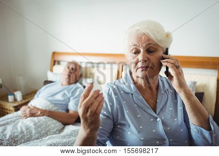Senior woman looking at pill bottle and talking on phone in bedroom