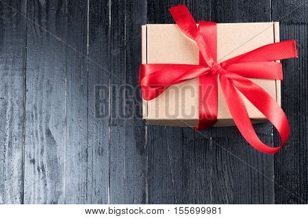 Natural paper box with red ribon bow on black natural wooden table. Christmas or Valentine's Day abstract concept. Copy space to the left.