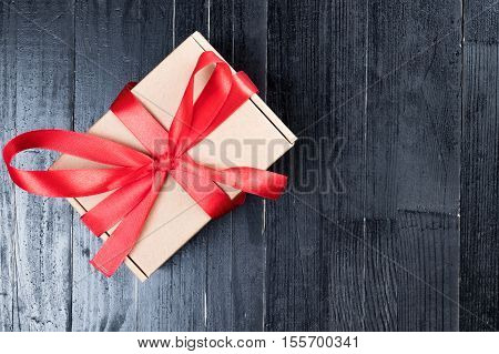 Natural paper box with red ribon bow on black natural wooden table. Christmas or Valentine's Day abstract concept. Copy space to the right.