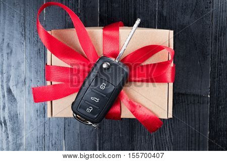 Car key on a paper box with red ribbon bow on black natural wooden table background. Christmas or Valentine's Day gift or present abstract concept.