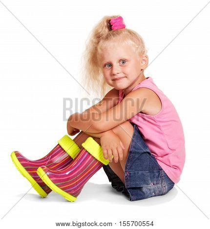 Little blond girl sitting in a pink blouse, blue skirt and colorful rubber boots isolated on white background.