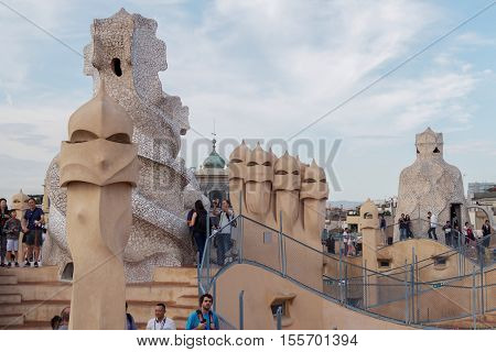 Barcelona, Spain - September 24 2016: Casa Mila La Pedrera rooftop tourists. Casa Mila La Pedrera in Catalonia, Spain was designed and constructed by architect Antoni Gaudi between 1906 and 1912.