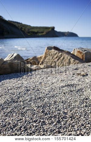 View on a beach with sand, round stones and beautiful blue sea water in the background, sunny day, selective focus
