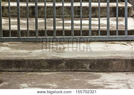 Close up of portion of galvanized metal gate and vintage concrete steps background