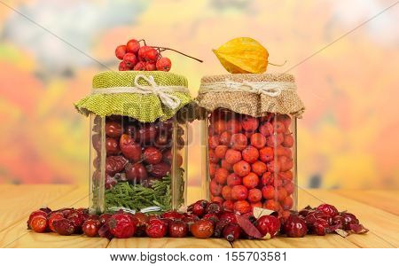 Jars with berries of mountain ash and wild rose on a background of autumn leaves