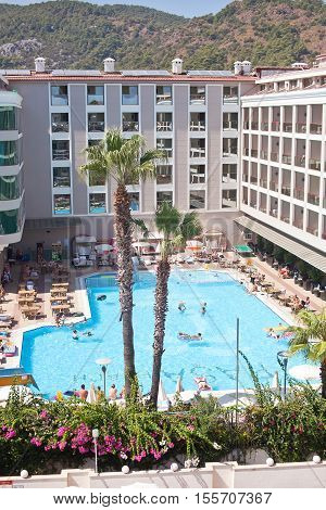 Marmaris, Turkey - 14 September, 2015: Luxury hotel with swimming pool. People swim in the pool and relaxing on sun loungers.
