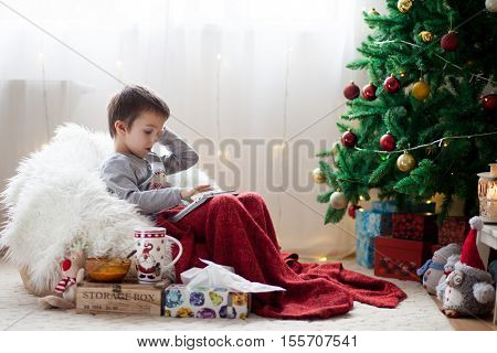 Cute Little Sick Boy, Sitting On Bean Bag, Playing On Tablet And Drinking Tea