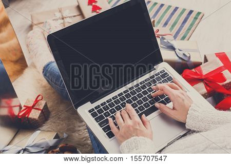 Christmas online shopping. Female buyer types order on laptop, copy space on screen. Woman buys presents prepare to xmas eve, among gift boxes and packages. Winter holidays sales poster