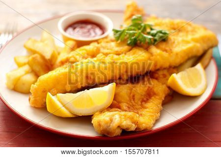 Two pieces of battered fish on a plate with chips