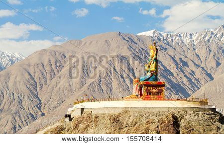 Giant Buddha Maitreya sitting statue in Nubra valley against the backdrop of the Himalayan mountains (Nubra northern India)
