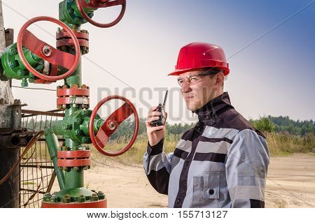 Oil field worker near wellhead valve wearing red helmet and work clothes talking on the radio. Oil and gas concept.