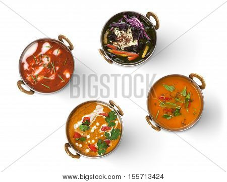 Vegan or vegetarian restaurant dishes, hot spicy and creamy indian soups and salads in copper bowls. Traditional indian cuisine meal assortment isolated on white background. Healthy eastern local food