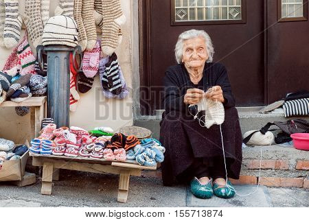 SIGNAGI, GEORGIA - OCT 7, 2016: Senior woman with sitting on the doorstep of home and knitting needles wool socks for family on October 7, 2016. Signagi of Kakhetia has a population 2.200