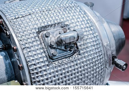 Details of gas-turbine auxiliary power unit. Nuts connecting tubes, nozzles, combustion chamber insulation. Industrial abstract background.