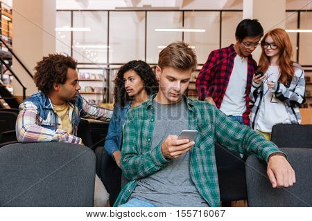Concentrated young man sitting in front of his friends and using mobile phone