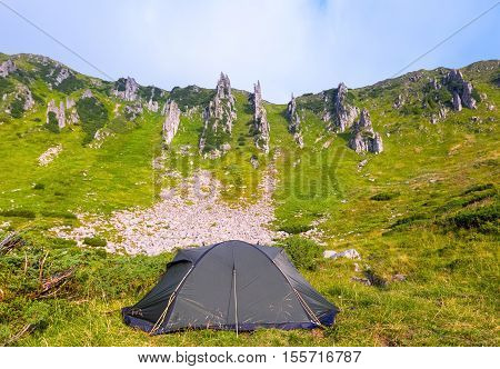 A solitary tourist tent stands on a meadow and around headlong rocky mountains a summer morning .
