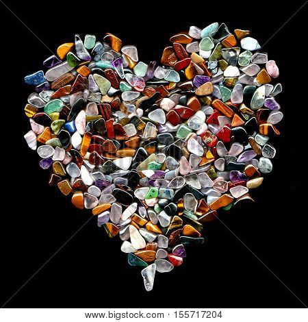 A Heart Shape Made Of Mixed Semi Precious Stones Isolated On Black poster