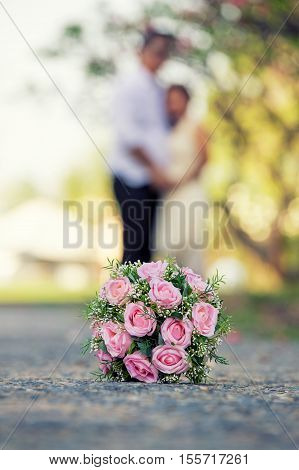 Newly married couple and wedding bouquet in the foreground. Wedding bouquet with the wedding couple in the background