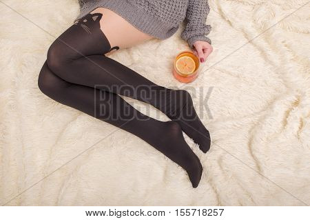 female feet in stockings with cup of tea on fur with copyspace