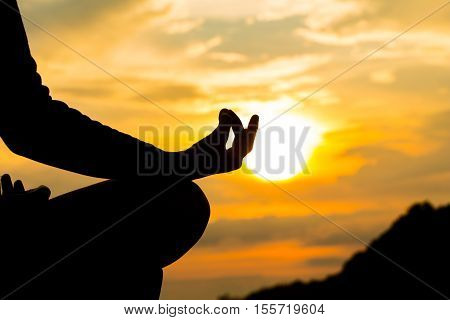 Silhouette, Hand Of Woman Meditating In Yoga Pose Or Lotus Position By The Sea At Sunset. Rear View.