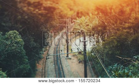 True tilt shift shooting of railway in jungle forest of Rio de Janeiro a lot of wires sunny summer day Brazil