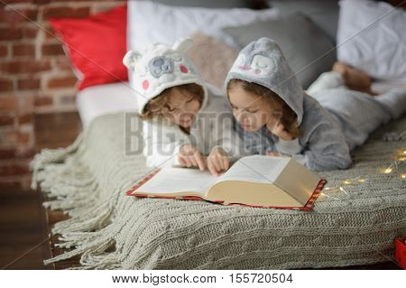 Two children brother and sister lie on big bed and read fairy tales. Children dressed in fluffy pajamas like little cute animals. Before them the huge book. Children are keen on reading.