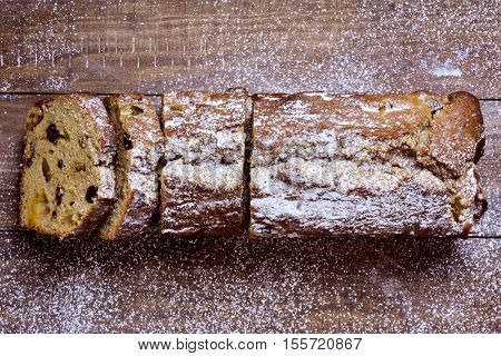 high-angle shot of a fruitcake for christmas time sprinkled with icing sugar, placed on a wooden rustic surface
