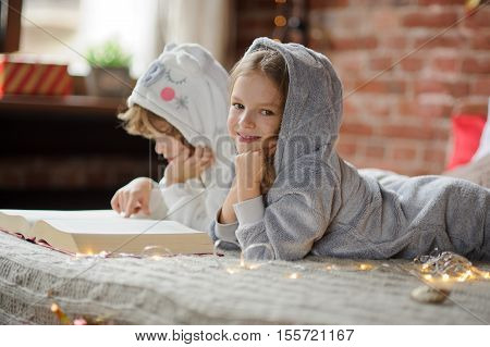 Christmas. Two children lie on the big bed and read Christmas tales. Children dressed in fluffy pajamas like little cute animals. Boy with interest looks in the book girl looks in camera and smiles.