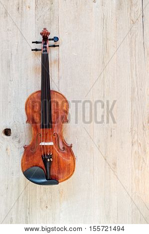 Top view of a standard violin made of wood on a weathered wood surface