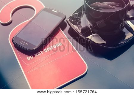 Do not disturbe sign a cup of tea and a mobile phone over dark background. Time for rest concept.