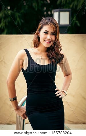 Happy Thai woman standing near swimming pool and posing for photo shoot
