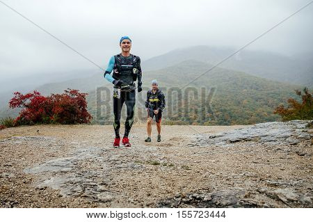 Yalta Russia - October 8 2016: two runners middle-aged men running in rain on a mountain trail during Crimea mountain marathon