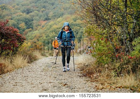 Yalta Russia - October 8 2016: middle-aged woman with walking poles traveling in rainy weather on mountain trail during Crimea mountain marathon