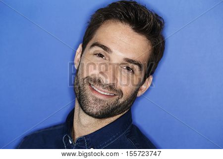 Smiling confident young man in blue studio portrait
