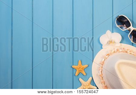 Beach accessories: hat, sunglasses, starfish and orchid flower on wood background painted in blue.