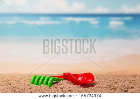 Children's toys shovel and rake in the sand on the sea background.