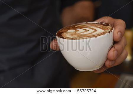 expert barista close up hands presenting delicious coffee with milk cream decorating foam on mug at coffee shop restaurant in cafe professional preparation concept
