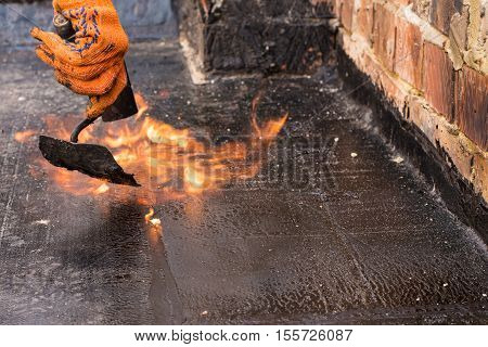Flat roof installation. Heating and melting bitumen roofing felt. Flat roof repairing with roofing felt. Roofing felt. Roofing repair. Roofer working. Roofer make. Roofer working tool. Waterproofing