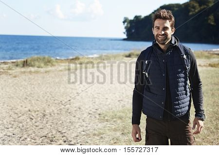 Smiling handsome hiker at the beach portrait