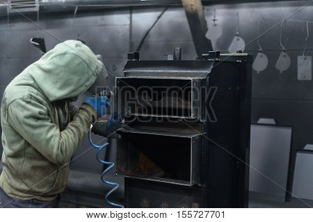 Worker sprays black paint on solid fuel boiler