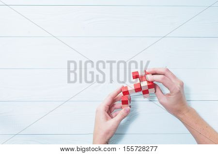 Logic background. The concept of logical thinking. Wooden colorful cubes puzzle. Hands holding wooden conundrum.