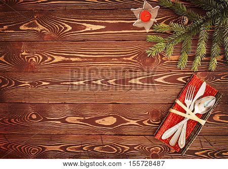 Greeting card for Christmas dinner and New Year's Eve Dinner. Silverware on wooden table: knife fork spoon. Holiday decorations: fir tree branch and red Christmas candle. Top view. View from above. Copy space