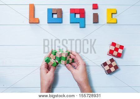 Logic background. The concept of logical thinking. The word of logic of multi colored wooden blocks on a wooden background. Hands holding wooden cubic.