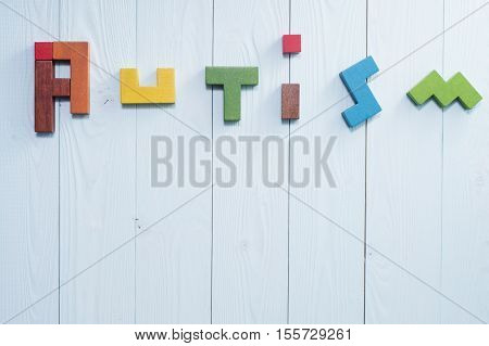 Word Autism built of colorful wooden blocks on a blue wooden background with copy space top view. Concept of autism word flat lay. Autism Spectrum Disorder (ASD).