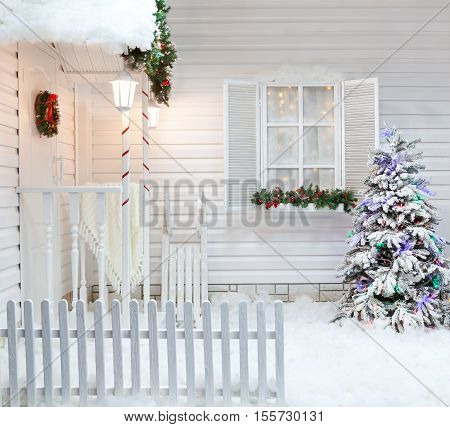 Winter exterior of a country house with Christmas decorations in the American style. Snow-covered courtyard with a porch tree and wooden vintage sleds.