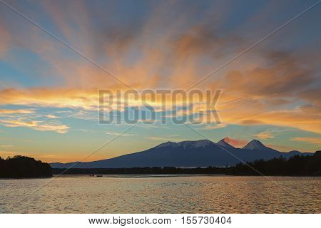 Beautiful sunrise over the volcanoes Kluchevskaya group with reflection in the river Kamchatka.